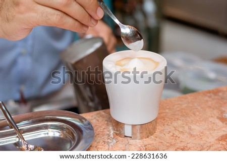 A barman is preparing a cappuccino - stock photo