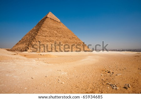 A barren desert and the rear of the Pyramid of Khafre looking onto a view of Cairo, Egypt. - stock photo