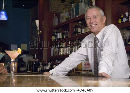 a bartender standing at a bar - stock photo