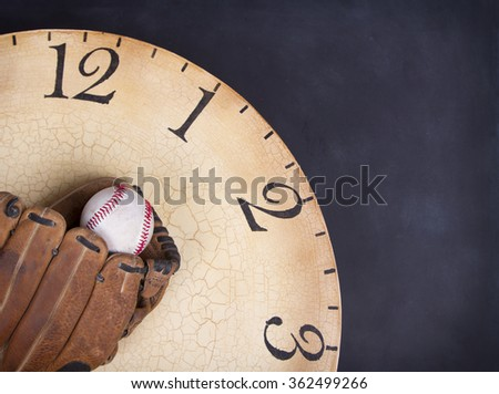 A baseball and mitt on an old vintage clock on a black background - stock photo