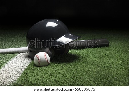 A baseball batting helmet bat and ball on a field with a white stripe and dark background