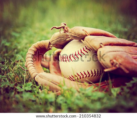 a baseball in an old glove on a grass background toned with a vintage retro instagram filter  - stock photo