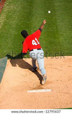 a baseball pitcher throwing a pitch with copy space - stock photo