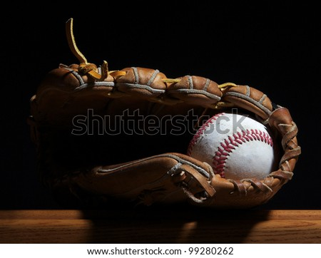 A baseball sits in a mitt on a wood bench set against a dark background. - stock photo