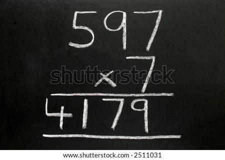 A basic multiplication sum on a blackboard. - stock photo