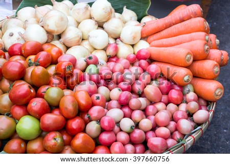 A basket filled with bright-colored vegetables including carrots, grape tomatoes, tomatoes and a pile of onions on a stall at a grocery store in Thailand - stock photo