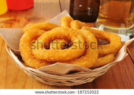 A basket of breaded onion rings with a glass of beer - stock photo