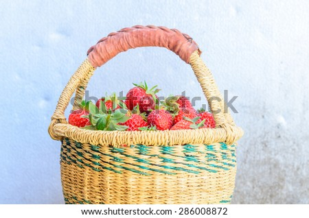 A basket of fresh organic strawberries with vintage background. These strawberries are handpicked from an organic farm in Puyallup, Washington State, US.  - stock photo