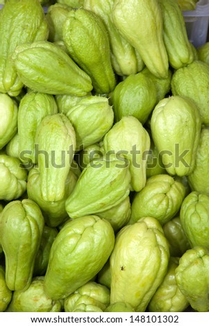 A basket of green, ripe chayote, Sechium edule, vegetables for sale at a roadside market. - stock photo