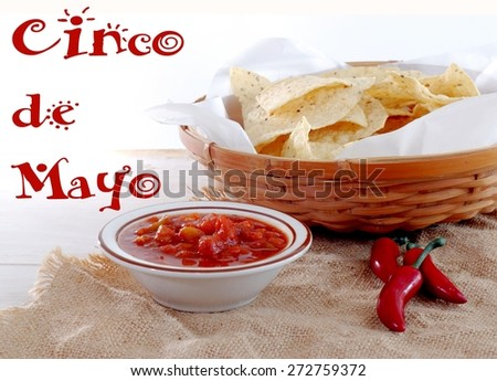 A basket of tortilla chips with a bowl of hot chunky salsa and some red peppers laying on a piece of burlap on a rustic wooden table. Cinco de Mayo message. Reddish orange is prominent color