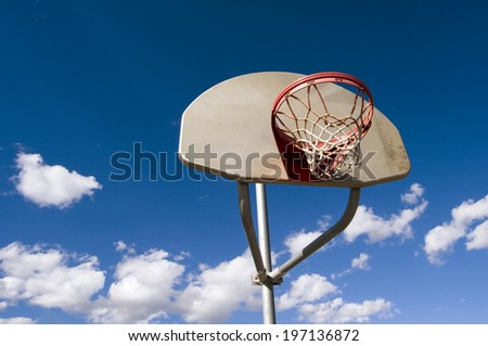 A basketball hoop against a blue sky backdrop with white fluffy clouds. - stock photo