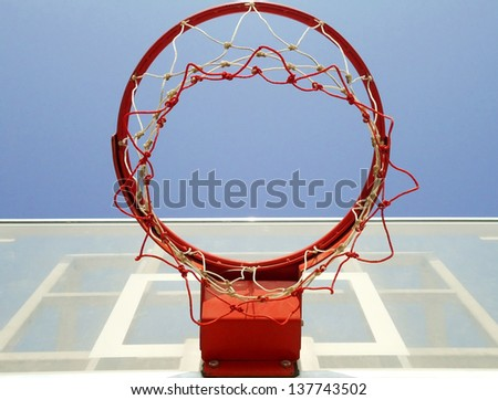 A basketball hoop, net and backboard on a playground, shot from below. - stock photo