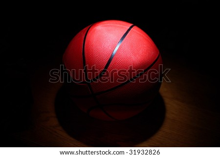 A basketball in the spotlight on a wood floor
