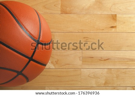 A basketball on a wood gym floor viewed from above - stock photo