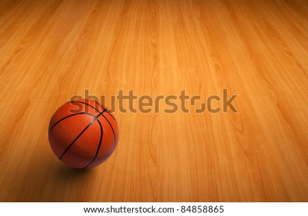 A basketball on the wooden floor as background - stock photo