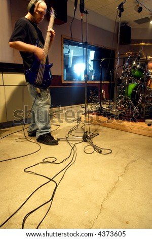 A bass player recording his tracks in a recording studio with natural outside light streaming into the control room.  Slow shutter speed with ambient light - player has motion blur from slow shutter. - stock photo