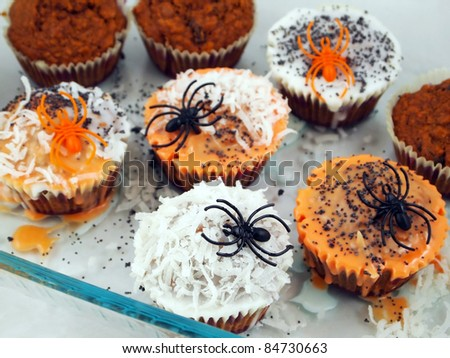 A batch of fresh homemade cupcakes being decorated for Halloween with spiders, colored frosting, and sprinkles. - stock photo