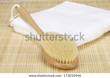 A bath brush is laying on a white folded towel. The scene is taken on a bamboo mat.