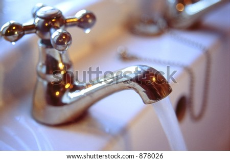 A bathroom tap with running water. - stock photo