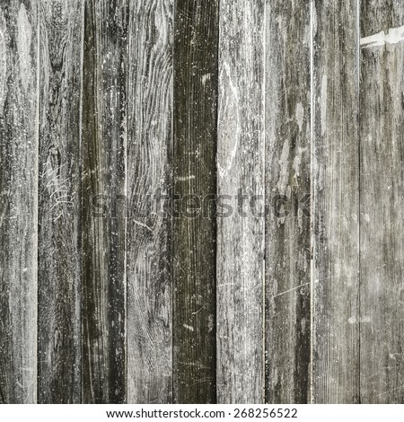 A battered old weathered wooden wall with scratched faded vertical plank panels. Textured wood grain abstract background with copy space. - stock photo