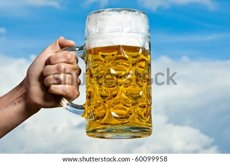 A Bavarian beer held against a blue and white sky - stock photo