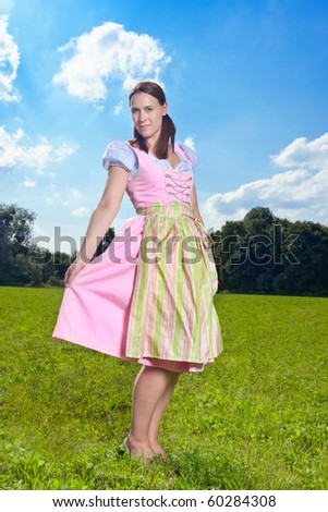 A Bavarian girl in a traditional Dirndl costume in a field with blue skies - stock photo