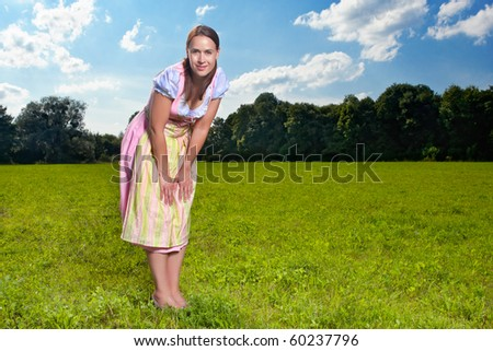A Bavarian girl in traditional costume in a meadow with blue skies - stock photo