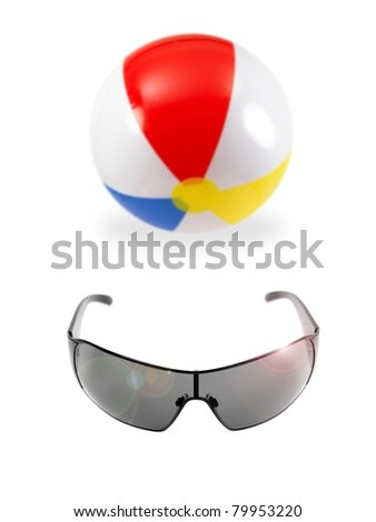 A beach ball and sunglasses isolated against a white background - stock photo