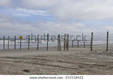 A beach made off limits to vehicles by a gated fence running across the beach and into the ocean in the Outer Banks of North Carolina