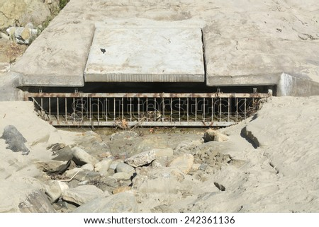 A beach sewer used to drain water runoff from the cliff side during heavy rains to control flooding - stock photo