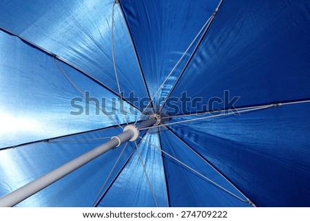 A beach umbrella blocks out the hot, tropical sun. - stock photo