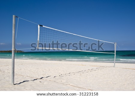 A beach volleyball net on a beautiful sunny day. Complete with white sand beach and turquoise sea. - stock photo