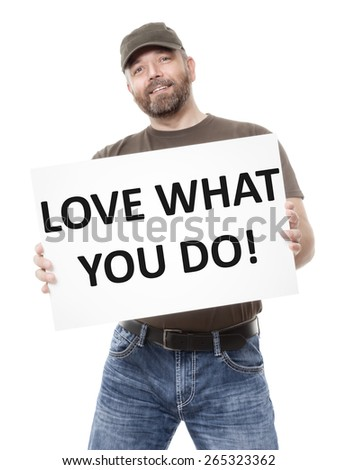 A bearded man holding a white board with the message love what