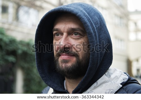 A bearded man in a hood on a city street - stock photo