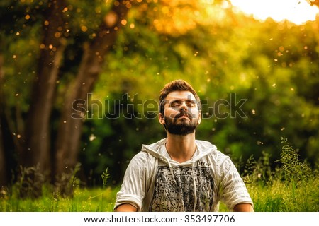 A bearded man is meditating on green grass in the park with face raised up to sky and eyes closed on sunny summer day. Concept of meditation, dreaming, wellbeing and healthy lifestyle - stock photo