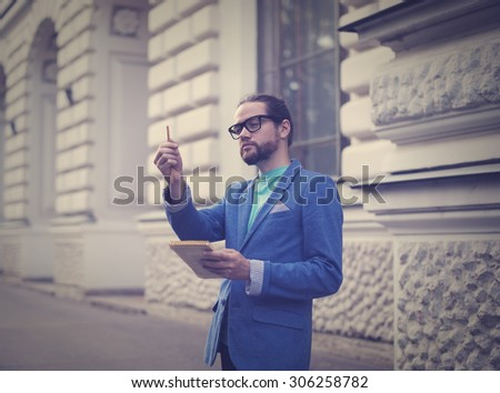A bearded man wearing glasses and a jacket, put his hand with a pencil and measure the future. - stock photo