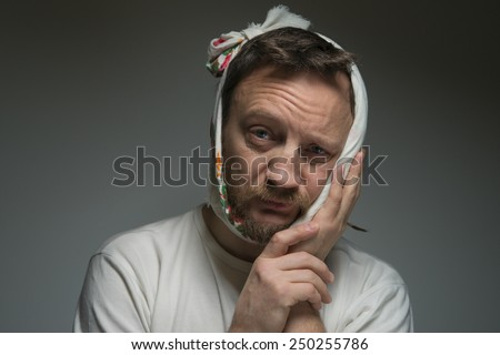 A bearded man with a bandage on his face. He has a toothache. - stock photo
