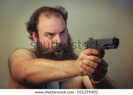 A bearded shirtless business man aims a firearm - stock photo