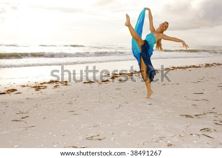 A beautiful adult female ballerina is dancing on the beach with her leg kicked up high looking at you the viewer wearing a long blue silk dress. With plenty of copy space.