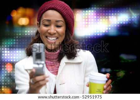 A beautiful African American business woman checking her cell phone in the city.  She could be text messaging or even browsing the web via wi-fi on a wireless broadband signal. - stock photo