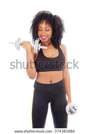 A beautiful African American girl working out with two dumbbell's inexercise outfit, isolated for white background, and smiling. - stock photo