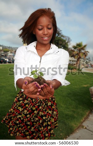 a beautiful african american woman holds a green plant in her hands - stock photo