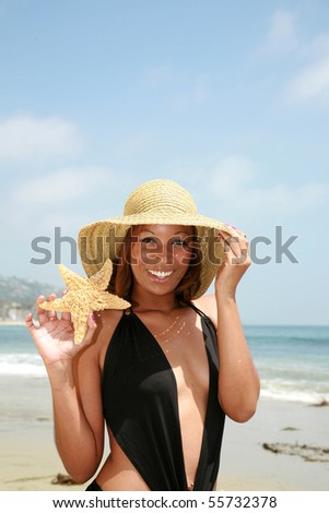 a beautiful african american woman shows off the star fish she found on the beach - stock photo