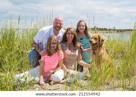 A beautiful American family sitting outside on a sunny day at the beach - stock photo