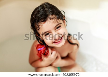 A beautiful and joyful girl is smiling in the bathroom while taking shower and looking straight at camera. - stock photo