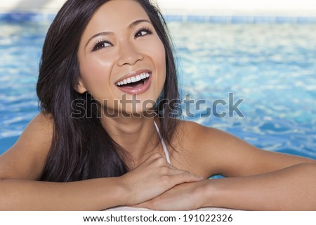 A beautiful and sexy young Chinese Asian woman wearing a white bikini leaning on side of a turquoise blue spa swimming pool. Healthy living and health club concept. - stock photo