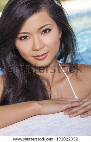 A beautiful and sexy young Chinese Asian woman wearing a white bikini leaning on side of a turquoise blue swimming pool. Spa, healthy living and health club concept. - stock photo