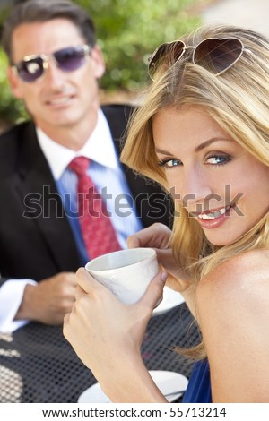 A beautiful and sophisticated young woman having coffee at a modern city cafe table with her friend a smart dressed businessman - stock photo