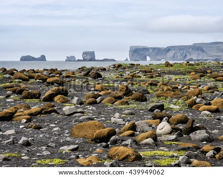 A beautiful and unusual landscape of large brown, black and gray volcanic rocks against the sea shoreline with volcanic outcrops in the distance