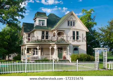 A beautiful and well maintained two story country home with white picket fence stands on the edge of a small rural town in Wisconsin. - stock photo